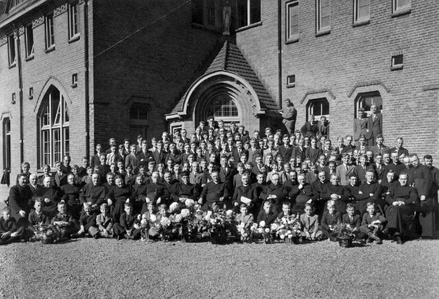 """065694 - Het St. Joseph-studiehuis van de paters van Mill Hill, in de volksmond bekend als """"de rooi pannen"""". bij de viering van het 25-jarig bestaan. Father A. Ahaus stichtte het St. Joseph-studiehuis van de Engelse St. Josephcongregatie van Mill Hill in 1912 aan het Wilhelminapark. Onder architectuur van Jan van der Valk werd in de jaren 1914-1915 aan de toenmalige Tongerlose Hoefstraat een nieuw studiehuis gebouwd."""