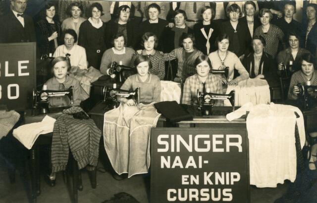 093088 - Onderwijs. Deelneemsters aan een naai- en knipcursus. Op de voorgrond reclema voor Singer-naaimachines.