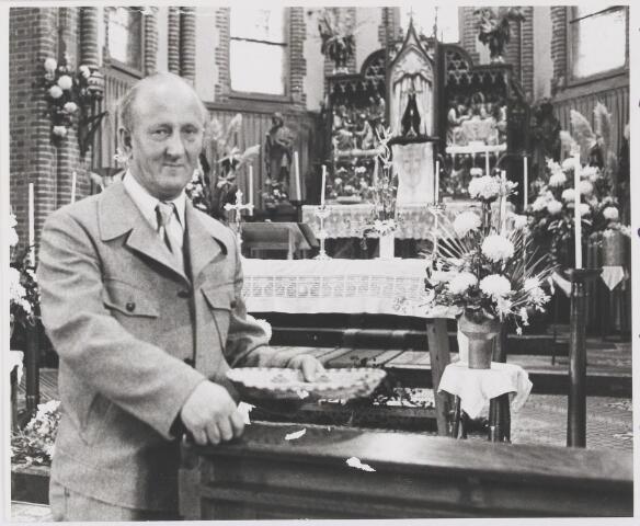 """081114 - Janus van Bavel, 1962 caféhouder, vanaf 2003 koster van Molenschot. Hier staat de """"koster"""" b.g.v. zijn zilveren huwelijksfeest, met zijn karakteristieke duim-pose als collectant in de St Anna-kerk. Behalve koster en caféhouder was hij ook een enthousiast carnavalvierder en hij zorgde ervoor dat de inwoners van Molenschot De Papslokkers werden genoemd in die periode."""