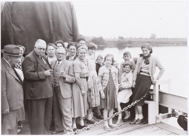 008894 - Bedevaart Tilburg-Handel-Kevelaar op de pont bij Bergen aan de Maas. Helemaal links grootvader A.P.A. Vos, geboren te Tilburg 1 oktober 1882, overleden aldaar 13 november 1955, kijkt naar zijn kleindochters W.Y.M. Vos geboren te Tilburg 30 januari 1944 en overleden aldaar 31 januari 1978, J.J.M. Vos geboren te Tilburg 23 april 1946, dochters van J.A.W. (sjef) Vos, geboren te Tilburg 29 april 1916. In het midden J. van Rijswijk * 1898, links daarvan J. de Kort (broedermeester) Goirkestraat fietsenzaak, links daarvan (grote dikke man) Govert Kolen.