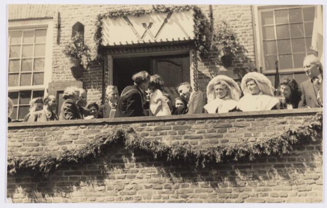101800 - Tussen Tilburg en Wolverhampton ontstond kort na de tweede wereldoorlog een speciale stedenband, die alles te maken had met de Prinses Irene Brigade, welke in Wolverhampton gelegerd was alvorens het Kanaal over te steken om mee te doen aan de bevrijding van onder meer Tilburg. Van 4 tot 11  mei 1946 kwam een heel gezelschap uit de regio Wolverhampton naar Tilburg voor een uitgebreide sportieve en culturele uitwisseling.  Tijdens dit bezoek bezochten ze ook Oirschot zoals op de foto op het bordes van het gemeentehuis.