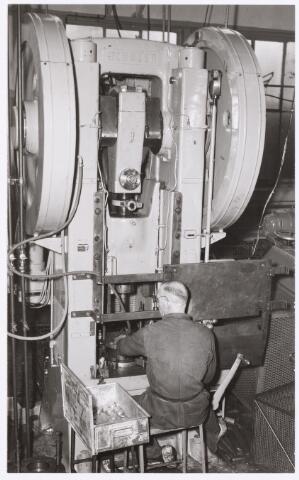 039035 - Volt. Zuid. Productie, fabricage van onderdelen in afd. metaalwaren ca 1956. Hier het extruderen van aluminium. Dit ging als volgt. Een aluminium plaatje of schijfje wordt in een stempel gelegd. De bovenstempel komt naar beneden en door de grote druk van de pers wordt het aluminium vloeibaar en kruipt langs de wand van de bovenstempel omhoog. Het vloeibare aluminium kruipt dus tussen de ruimte van boven- en onderstempel en neemt de vorm aan van het geweste model. Hiermee werden o.a. spoelbussen, spuitbussen, condensatorbehuizingen, scheerbrillen voor de Philishave,microfoonbehuizingen en vooral de statoren en rotoren van concentrische luchttrimmers (vele 100den miljoenen) gemaakt. In de normaal bak links van de man achter de pers liggen de te bewerken schijfjes (platines).