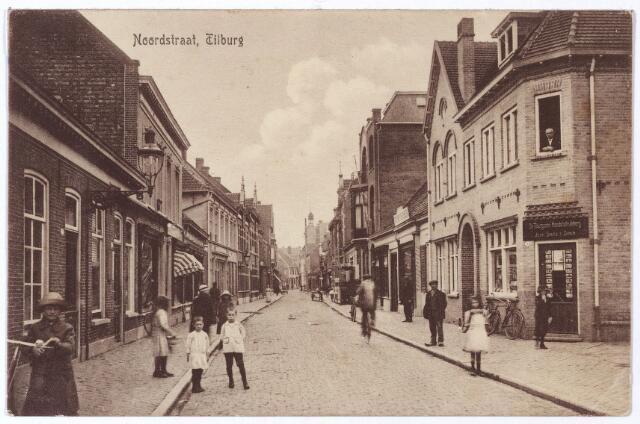 001718 - Noordstraat in de richting van de Nieuwlandstraat. Rechts Noordstraat nr. 83, de drukkerij van Jean Smits. Johannes Henricus (Jean) Smits kwam op zestienjarige leeftijd naar Tilburg, waar hij het drukkersvak leerde bij Antoine Arts op de Heuvel. In 1886 begon hij een eigen drukkerij op het adres Noordhoek M670, later Noordstraat 85. Rond 1914 verhuisde hij naar het nieuwe pand Noordstraat nr. 83. De firmanaam van zijn drukkerij was 'Tilburgsche Handelsdrukkerij Jean Smits & Zn. Er was ook een kantoorboekhandel aan verbonden. Kranten gedrukt bij Smits waren 'De Vooruitgang Nieuws en Advertentieblad', 'Tilburgsch Weekblad nieuws en advertentieblad' (1902), 'Tilburgsche Post, nieuws en advertentieblad (1921) en 'Tilburgsch Advertentieblad' (1928-1936). Voor het R.K. Gymnasium drukte Smits vanaf 1904 de boekenreeks 'Letterkundige Bibliotheek. Jean Smits overleed te Roermond, zijn geboorteplaats, op 20.9.1942 en werd begraven te Tilburg. Zoon Petrus J.M. (Piet) Smits vestigde zich als drukker en handelaar in schrijf- en kantoorbehoeften aan de Korvelseweg. Op het adres Noordstraat 83 woonde zoon Josephus H.B. (Jos) Smits, boekdrukker van beroep en te Haarlem op 22.7.1925 getrouwd met Henriëtte Suzanna Bosse. Hij was op het adres Noordstraat 83 boekdrukker en boekhandelaar, maar verhuisde later (vóór 1948) als boek- en kantoorboekhandelaar naar het adres Noordstraat 101. De Tilburgsche Handelsdrukkerij werd werd verplaatst naar het adres Schoolstraat 3.  Naast het pand Noordstraat 83 de ingang van het Burgerijpad.