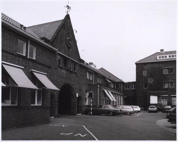 022973 - Elisabethziekenhuis. Achterzijde van de hoofdingang van het St. Elisabethziekenhuis aan het binnenplein. Dit gedeelte is voor de sloop gespaard en biedt  nu onderdak aan diverse instellingen. In het midden op de achtergrond de ingang naar het mortuarium