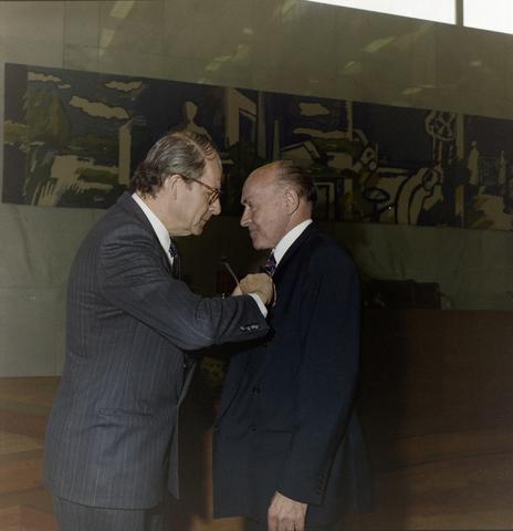 1237_012_970-2_001 - Koninklijke onderscheiding. Lintje. Lintjesregen bij de Gemeente Tilburg in april 1992. Burgemeester Gerrit Brokx spelt een lintje op in de vergaderzaal van Gemeente Tilburg.