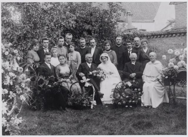 045892 - Op 6 augustus 1920 hertrouwde te Goirle fabrikant Jan van Besouw, weduwnaar van Elisabeth Maria Louise van den Heuvel, met Johanna Maria Vromans. De foto werd genomen in de tuin van zijn villa aan de Tilburgseweg. Op de eerste rij v.l.n.r. zijn getuige en schoonzoon Johannes Cornelis Petrus Mes, geboren te Wijchen op 1 november 1882, bedrijfsleider, later directeur van de N.V. Stoomweverijen Van Besouw, zijn vrouw Johanna Emiliana Maria van Besouw, geboren te Goirle op 8 januari 1889, haar vader Jan Baptist Maria van Besouw, geboren te Goirle op 4 oktober 1861, de bruid Johanna Maria Vromans, geboren te Goirle op 31 mei 1892, haar vader, wever Franciscus Vromans, geboren te Goirle op 12 juli 1862 en de dominicaan pater A. Rijken. Op de achterste rij v.l.n.r. Maria Gerardina Josephina (Iet) van Besouw, geboren te Goirle op 23 december 1894, haar man Christiaan Johannes Adriaan Kerstens, geboren te Bergen op Zoom. Hij was veearts te Maastricht, directeur van het gemeentelijk slachthuis te Roermond en veterinair inspecteur te Breda. Vervolgens een onbekend meisje, luitenant Jannes Jonker, geboren te Nijmegen, en zijn vrouw Emma Maria Dominica Gerarda van Besouw, geboren te Goirle op 23 december 1894. Achter dit paar father dr. Hubertus H. Ahaus, geboren te Dordrecht op 26 juli 1877  en door het oorlogsgeweld om het leven gekomen te Nijmegen op 18 september 1944. Hij werd begraven te Tilburg, waar door zijn toedoen het klein seminarie van de St. Josephcongregatie van Mill Hill tot stand kwam. Vervolgens Lambert Poell, geboren te 's-Hertogenbosch op 22 maart 1878, vanaf 1915 pastoor te Gemert en pionier van de katholieke sociale beweging. In Tilburg zette hij in 1897 een cursus op over de katholieke sociale beginselen. Hij was er kapelaan van de St. Annaparochie, toen hij in 1905 de textielarbeidersbond St. Severus oprichtte. Van 1904 tot 1915 was hij geestelijk adviseur van de mede door hem tot stand gekomen Nederlandse R.K. Textielarbeidersbond St. Lambertus. 
