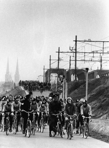 1238_F0383 - Grote groep fietsers rijdt over een spoorviaduct. Poltieagent, CDA