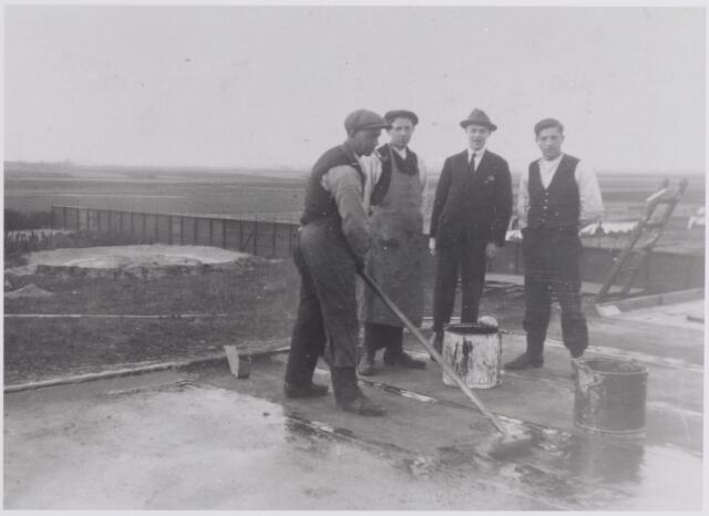 045842 - Het teren van het dak van een bedrijfsgebouw van Pijnenburg's Weverijen N.V. te Goirle. Links Jan van der Zande. Op de achtergrond de Kerkakkers en verder weg het gebied van de Grote Akker. Enkele jaren later zou in het gebied van de Kerkakkers het Oranjeplein worden aangelegd.