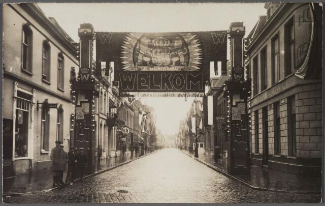 011207 - Stationsstraat vanuit de Spoorlaan. Bij de ingang een ereboog ter gelegenheid van het bezoek van koningin Wilhelmina aan Tilburg. Zij kwam naar de stad voor de onthulling van het standbeeld van koning Willem II op de Heuvel.