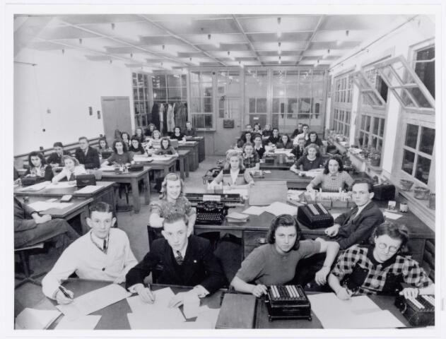 """039425 - Volt, Zuid. Hulpafdelingen, Administratie. Foto ter gelegenheid van het 25-jarig jubileum van Dhr. van de Zilver, hoofd van de afdeling Loonadministratie, op 27 juni 1946.  Deze foto is ook gepubliceerd in het Brabants Dagblad op 03-10-2000 in de rubriek '""""weerzien"""".  Op de foto achtereenvolgens de tafels aan de linkse kant v.l.n.r.:  tafel 1; Sjan v. Spaendonk en Annie de Leeuw. tafel 2 Ad v. Griensven, Hans Meijers en Belia de Weert. tafel 3 Annie Mutssaers, Jacky Neggers en Nelleke Jansen. tafel 4, Riet Zoetmulder, Riet in 't Groen en Rini Loode. tafel 5 Riet Vermeer en Tilly de Reuver en de laatste tafel of buro Noud van Kollenburg. De tafels of buro's aan de rechtse kant van voor naar achter en v.l.n.r.: tafel 1  Oprinsen, Martijn Huijbregts, An Okkeloen en Riet Verhoeven. tafel 2 Corrie Vermeer en   Kees Adams. tafel 3 Riet Middelman en Riet v. Heezik. tafel 4 Annie Oostelbos en Will van Pelt. tafel 5 Piet Theunis en Ben Loodestein. tafel 6 Toos Burgers, Riet v. Es en Ria Adams. tafel 7 Gerard Donders, Jan Bezems en Jan v. Herwaarden en de laatste tafel Annie v.d. Ven, Riekie v. Loon en Theo de Vroe.Voltstraat was toen Nieuwe Goirleseweg genaamd."""
