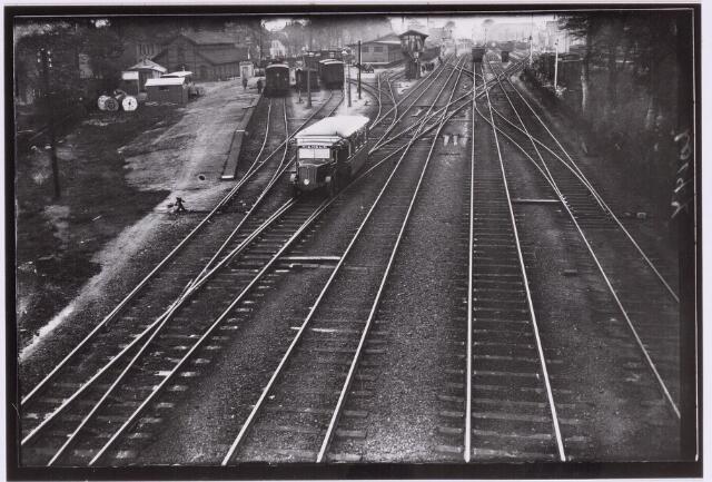 """036762 - Spoorwegen, Centrale Werkplaats, Atelier, NS: IS HET EEN TRAM, IS HET EEN AUTO, IS HET EEN TREIN ?  De """"Micheline""""-auto schiet met spookachtige snelheid over de  ijzerenweg. Wij hebben vandaag, 4 mei 1932, de Micheline-auto ge fotografeerd. Of de benaming """"auto-op-rails"""" wel juist is; we weten het niet. 't Is geen trein, 't is geen auto, 't is haast een trambus. Dit staat vast, dat de wagen met grote snelheid over de lijn stuift, nl. ca. 60 km per uur. Wij fotografeerden de Micheline te Tilburg bij het verlaten van het station. De opname is gemaakt vanaf de luchtbrug bij de Koestraat."""