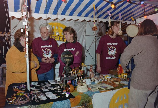 1237_001_037_017 - Vrijwilligerswerk. Vrijwilligers. Een feestelijke bijeenkomst van Stichting Contour in Theater De Vorst (tegenwoordig theater de Nieuwe Vorst) in december 1997. De stand van de Wereldwinkel op de informatiemarkt.
