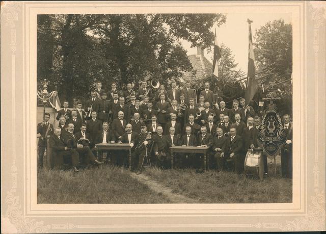 830087 - Groepsfoto Koninklijke Harmonie Concordia van Hilvarenbeek. bestuur en muzikanten. De Koninklijke Harmonie Concordia, opgericht in 1839, gefotografeerd op de markt in 1912 bij gelegenheid van een festival. De volgende personen zijn er op te herkennen: zittend van links naar rechts: N. de Brouwer, gemeentesecretaris; A. de Bruyn, hoofd der school in Esbeek; N.N.; J.C. de Rooij, burgemeester; Ja. Willekens; Aem. Huismans, notaris, in de uniform van commandant der rustende schutterij; Ant. Verhoeven; P. Bressers; dokter Scheidelaar, arts, voorzitter; G. van Mourik, bestuurslid, Hub. Heezemans, oud-directeur, hoofd der school; F. Damen, leerlooier;  voorste rij staand, met schelleboom N.N.; J. Spieringhs; A. Dekkers; C. Mallens; Jac. van der Vleuten; J. Favier; E. Palmen; meester Kemps; H. Swinkels, bierbrouwer; meester Tooten; J. Jacobs; Jac. Naaykens; meester De Bruin; J. Smolders; Jan Heeren, met trom; P. Prinsen, met vaandel;  tweede rij staand, A. van Raak; Fr. Heezemans; A. Visser; H. de Laat (soldaat); P. van Raak; P. de Laar; Jan Jansen; M. Frick; J. Kluytmans; W. van der Wiel; Jan Smolders; Mart. De Graaf; H. Blankers; W. Heeffer; J. van den Broek; Hub Beckers; J. Heeren; H. Heeren; A. Heeffer, met vlag; achterste rij M. Kronenburg; Jac. Brekelmans; A. Blankers; E. Naaykens; J. Rademakers; J. Brekelmans; C. Stads; A. Hoes.