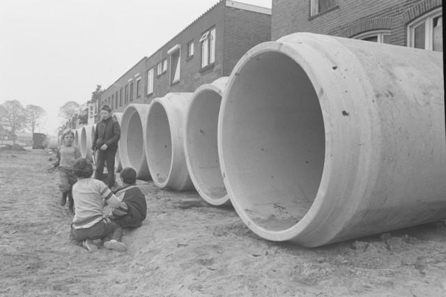 """TLB023000016_002 - Spelende kinderen bij rioleringsbuizen ten behoeve van aanleg van een nieuw rioleringsstelsel. Foto gemaakt ten behoeve van de Begrotingskrant van Tilburg, waarin wordt aangegeven dat de stad financieel gezond is als gevolg van het """"Tilburgs Model""""."""