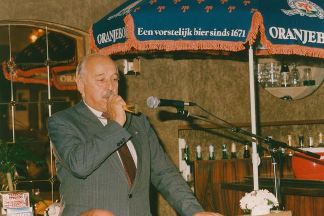 651324 - Tilburg, 125 jaar stad aan het spoor. Manifestatie. Op het einde van de zaterdagochtend is er al veel belangstelling voor de tentoonstellingen (i.v.m. de Manifestatie) in de zalen van de Nieuwe Koninklijke Harmonie in de Stationsstraat. De voorzitter van de stichting  de heer Van der Veen spreekt een welkomstwoordje  en de heer Van Spaendonck, lid van het committee, verhoogt de feestvreugde met een stoor op een rangeerhoorn.
