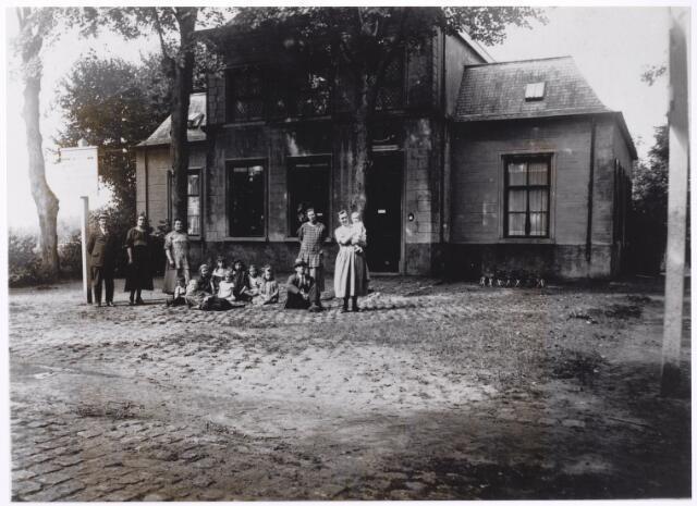 """046552 - Douanekantoor bij de grensovergang Goirle - Poppel aan de Poppelseweg. Voor de aanleg van de Poppelseweg was het grenskantoor gevestigd op Rovert, maar bij K.B. van 3 september 1855 werd """"het kantoor van expeditie voor het inkomen aan de landzijde, zijnde te gelijker tijd kantoor van laatste visitatie bij het uitgaan"""" opgeheven, en m.i.v. 1 oktober 1855 verplaatst naar de Poppelseweg in Goirle. De bouw van het nieuwe kantoor werd reeds in 1854 gegund aan H. van Rooij uit Waalwijk, na goedkeuring tot aanbesteding van de minister van binnelandse zaken, Van Reenen. De inschrijving vond plaats op 17 oktober 1854 in """"het lokaal van het provinciaal bestuur te 'S-Hertogenbosch"""". Het complex bestond volgens een bestek uit 1875 uit """"een hoofdgebouw bestemd tot woning van den ontvanger en de commiezen, een visitatieloods met drie bergplaatsen, een bakhuis met pomp en bakoven, en een houten loods ingericht tot drie stallen"""". Op de foto het kantoor met ontvangershuis. Geheel links ontvanger Gerrit Jan Klein Paste. Derde van links diens vrouw, Cornelia Wilhelmina van Andel."""