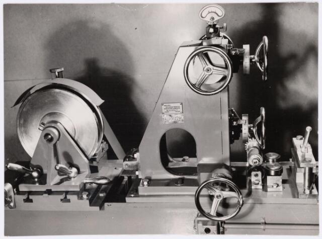 039006 - Volt. Zuid. Productie. Fabricage. Condensatoren. Walserij. Detail micro schaafmachine voor het schaven van messingband waaruit condensatorplaatjes werden gestanst. De dikte van het te schaven materiaal moest en kon op ± 0,001 mm nauwkeurig zijn. De dikte instelling geschiedde met de handwielen. Bovenaan staat een micrometer welke op 1/1000 mm kon worden afgelezen. Locatie gebouw C.