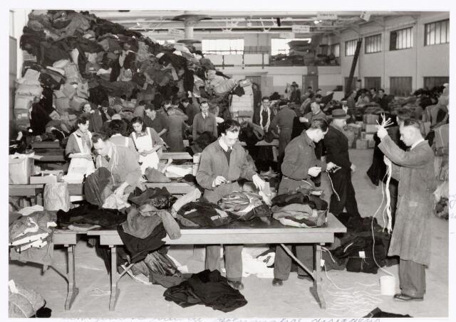 039344 - Volt. Zuid. Hulp-afdelingen, Sociale Zaken, Zorg. Op 1 februari 1953 viel Zuid-west Nederland ten prooi aan een enorme watersnoodramp. Inzameling bij het Volt personeel leverde inclusief twee vrijwillige overuren een bedrag op van fl. 8750. Dat was ongeveer fl. 3,00 per persoon hetgeen voor die tijd veel was. Immers de bruto lonen in die tijd bedroegen amper fl. 18 per week. De directie van Volt vulde dit bedrag aan met nog eens fl. 11.350. Verder stelde Volt een complete fabricagehal ter beschikking voor het verzamelen,  bundelen en verzenden van de hulpgoederen. Van Volt mochten bij toerbeurt per afdeling 20 tot 30 medewerkers hieraan meewerken. Verdere hulp kwam van de leerlingen van de textielschool, studenten, militairen, personeel van gemeentewerken en huisvrouwen van werknemers. De coördinatie van het geheel was in handen van Mw. Kipperman, de echtgenote van de toenmalige directeur.