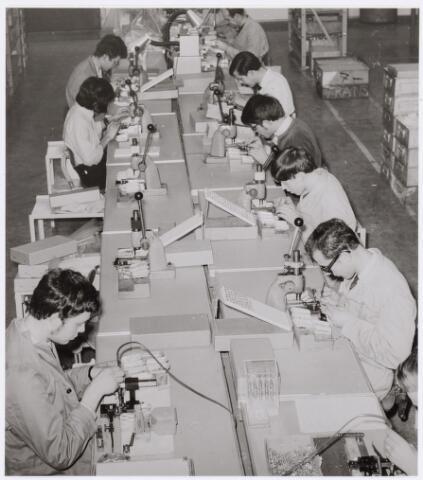 039008 - Volt. Zuid. Hal Z. Condensatoren. Trimmers. Fabricage. Productie. Knooptrimmermontage. Hier nog handmontage ( 1960-1970 ).  In 1970 kwam de eerste volledig geautomatiseerde lijn klaar. Knooptrimmers zijn mini instelcondensatoren en werden gebruikt om circuits af te regelen. Zij vervingen de daarvoor in gebruik zijnde concentrische luchttrimmers die qua volume veel groter waren.