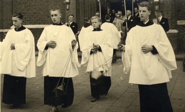 092885 - Op 4 september 1955 werd door mgr. W. Mutsaerts de nieuwe parochiekerk aan de Gasthuisstraat, de kerk van O.L.V. van Altijddurende Bijstand, ingewijd. De foto werd genomen bij het verlaten van de oude parochiekerk, toegewijd aan de H. Vincentius a Paulo. Onder baldakijn pastoor Jansen. De acolieten op de voorgrond zijn v.l.n.r.: Piet Bertens, Paul van Nunen, Jac van Ginderen en Wil van den Hout.