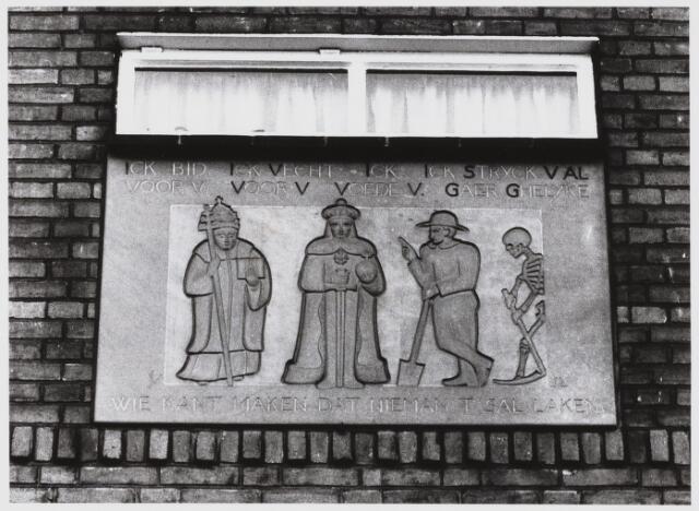 """068107 - GEVELSTEEN MET HET DEVIES: """"DE DOOD MAAKT ALLEN GELIJK"""". Vermoedelijk is deze steen van rode zandsteen gemaakt n.a.v. het overlijden van C.J.J. Wouters (1851-1935), de vader van de latere bewoner, handelaar in wol C.C.M. Wouters (1894-1949) . De afbeelding is een variatie op het thema van de Dodendans, dat in de late middeleeuwen vaak werd afgebeeld. Ondanks het aangebrachte monogram, is het niet gelukt de maker te achterhalen.  Trefwoorden: Kunst, openbare ruimte, woonhuizen"""