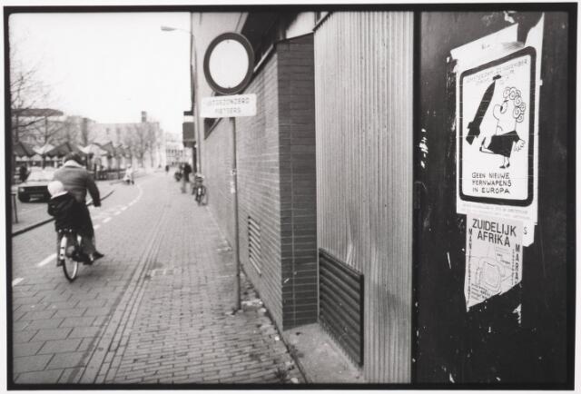 033575 - Achterkant van Vroom & Dreesmann (V & D) aan de Tuinstraat met daarover  het rode fietspad en de fietsenstalling aan het Pieter Vreedeplein. Op de schutting affiches Zuidelijk Afrika,  kernwapens.