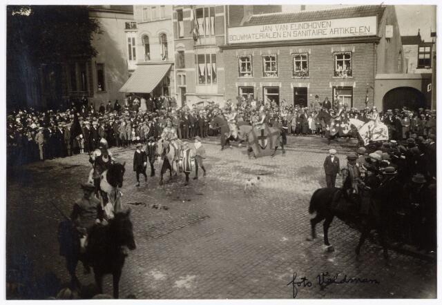 048913 - Optocht ter gelegenheid van de kroningsfeesten bij het 25-jarig jubileum van koningin Wilhelmina (1923-1924) deelnemers verzamelden zich op de Kromhout kazerne te Tilburg. Hier trekt de stoet over de Heuvel. op de achtergrond de firma Jan van Eijndhoven bouwmaterialen en sanitaire artikelen. links naast het luifel is de Veemarktstraat.