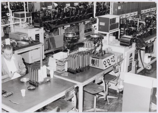 """038988 - Volt. Zuid. Fabricage. Productie. Afdeling Condensatoren, Trimmers. Op de voorgrond het controleren van magazijntjes met onderdelen die gebruikt werden op de volledig automatische montagestraat voor knooptrimmers, rechts en achteraan zichtbaar.  Knooptrimmers waren in feite de geminiaturiseerde opvolgers van de fameuze conbijluco`s (concentrische bijstel lucht condensator) gemaakt van aluminium, die bij Volt welhaast miljarden gemaakt zijn, Het hiertoe gebruikte procedé was het  in een klap """"spuiten"""" ofwel extruderen van een aluminium platine (plaatje) via een pers met een zodanig hoge druk dat het aluminium als het ware vloeibaar werd en omhoogspoot rond een negatieve vorm van het eigenlijke product.  De grondlegger van dit voor Volt zo succesvolle procedé was Ir. Lambeek die van 1934 tot 1939 bedrijfsingenieur was.  In 1979 is het restant van de productie van de conbijluco en het spuitprocedé over gedaan aan Philips Zwolle. Links op de foto Toon Pistorius."""