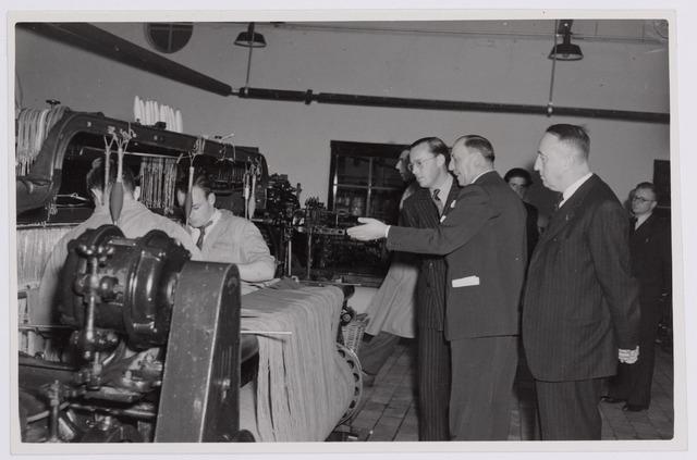 037652 - Textielindustrie. Textielindustrie. Textielindustrie. Prins Bernhard wordt op 13 november 1950 rondgeleid in wollenstoffenfabriek H. F. C. Enneking. Hier is het gezelschap in de weverij, waar prins Bernhard kijkt naar twee aandraaiers. Zij draaiden de draden van de nieuwe ketting vast aan die van de oude