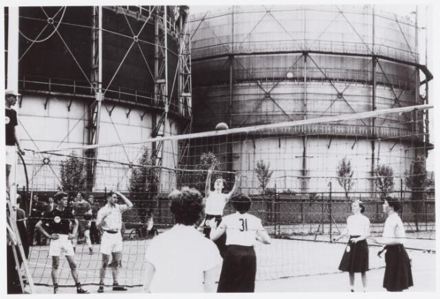 054291 - Sport. Volleybal. Bij gebrek aan een behoorlijke zaal werd de volleybalcompetitie midden jaren vijftig in de open lucht gehouden in de speeltuin van de parochie Theresia. waar op 3 velden kon worden gespeeld. Op de achtergrond de gashouders van het gemeentelijk gasbedrijf.