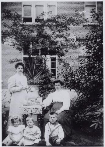 049966 - Theevisite bij de familie Van Breda-Hamers. Staande links Catharina Maria Hamers, geboren te Tilburg op 24 januari 1874 en aldaar overleden op 14 mei 1951, dochter van juwelier Adrianus Hamers en Elisabeth Maria Castelijns. Zij was getrouwde met Augustinus Johannes van Breda, banketbakker van beroep. Zittend rechts haar zus Anna Maria Hamers, geboren te Tilburg op 25 december 1876 en overleden op 27 juli 1940. Zij was getrouwd met de Goirlese textielfabrikant Cornelis H. Peijnenborg. Rechts op de voorgrond haar zoon Godfried Peijnenborg, geboren te Goirle op 17 maart 1902 en overleden te Tilburg op 12 maart 1980. Links twee kinderen Van Breda.