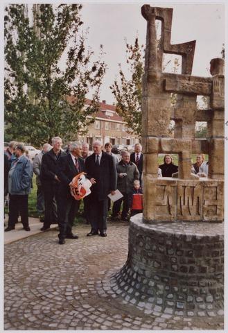 050102 - Volt, Algemeen, Kunstwerken, Onthulling, Voltvonk. Op 30 oktober 2002 werd dit monument opnieuw onthuld op het Transvaalplein, een locatie dicht bij het oude Voltterrein. Na de onthulling praatte Burgemeester Stekelenburg ( met doek ) nog na met Ir. Hoevenaars. Achter de Burgemeester herkennen we de heer van Rouwendaal, oud veiligheidsfunctionaris van Volt, en schuin achter Hoevenaars met groene jas Jozef van Coolegem, hoofd van een onderhoudswerkplaats. Geheel links in blauw jack Ad Godefroy en tussen de Burgemeester en Hoevenaars Piet van Loon.