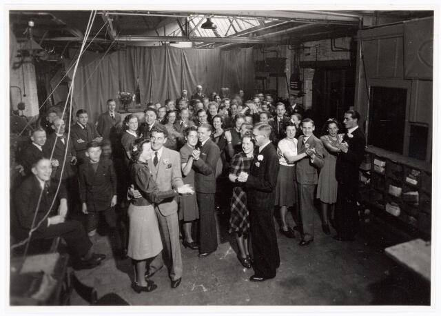 038460 - Schoenindustrie. Interieur montagehal N.V. Simon Heymans lederwarenfabriek aan de Watertorenstraat. Foto genomen b.g.v. het 25-jarig dienstjubileum van de heer Prince procuratiehouder in 1941.