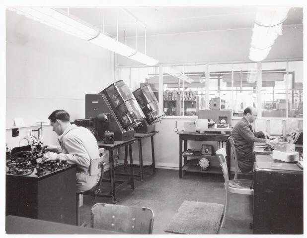 038906 - Volt. Zuid. Electro-Technisch Laboratorium, E.T.Lab.in gebouw S.Ca.1955. Een kijkje in de standaardmeetkamer met links de Hr.Bart Reinhout en rechts de Hr.Frits de Wilde. Hier stonden de standaard meetapparaten waarop de fabricage meet-apparatuur werd afgeijkt. De afdeling ging later op in E.B.M., Electrische Bedrijfs Mechanisatie en nog later werd de naam PS&A, Productie  Systemen en Automatisering.