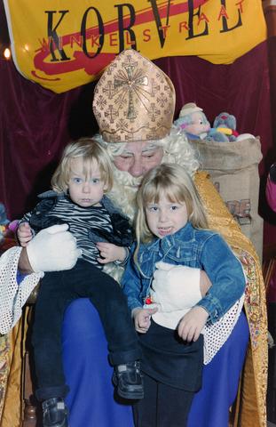 1237_001_003_006 - Feest. Korvel Winkelstraat. Sint Nicolaasviering. Twee meisjes poseren met Sinterklaas tijdens een Sinterklaasfeest georganiseerd door winkeliersvereniging Korvel Vooruit op 27 november 1999.