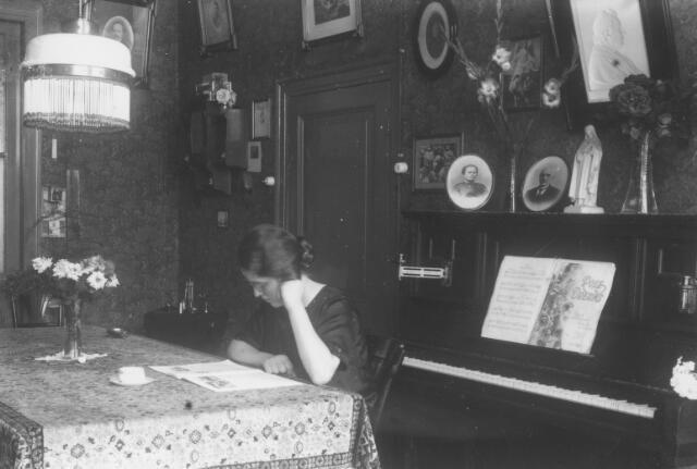065734 - Interieur van de woning van architect Ide Joannes Bloem aan de Telefoonstraat 29. Aan de tafel zijn vrouw Maria J.C.J. Bogaerts geboren te Tilburg op 10 januari 1894, dochter van Manilius A. Bogaerts, fabrikant van landbouwmachines, en Johanna C. Brekelmans. Bloem werd geboren te Hoorn op 24 november 1893 en was in Tilburg in 1926 een van de oprichters van de vereniging van Tilburgse beëdigde makelaars. Zijn dochter Anny trouwde de Tilburgse architect Jos C.A. Schijvens. Op de piano een beeldje van de H. Theresia van Lisieux.