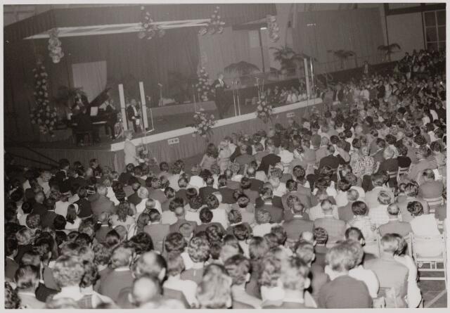 """050110 - Volt. Het 60 jarig jubileum van Volt werd gevierd in de stadssporthal in Tilburg op 5 en 6 september 1969. Het totale aantal bezoekers was 7000. Het feestprogramma was een amusementsshow onder de titel; """"Een avondje uit"""". De muziek werd verzorgd door het Radio Romantica Orkest en tijdens de pauze natuurlijk harmonie Volt. Overige deelnemers o.a. Cees de Lange, The Sheperds, Mr. Joe Andy, Ria Valk, John Woodhouse, Corry Brokken met aan de vleugel Jack Schutte, het Leedy Trio, The Three Jacquets, Toby en Jerry Rix en André van Duyn, die op deze foto met zijn optreden bezig is."""