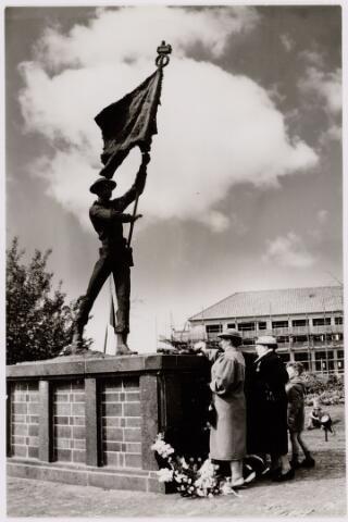 049430 - Bloemenhulde bij het beeld voor de Irenebrigade aan de Ringbaan-Zuid. Het beeld werd onthuld door prinses Irene in 1955 en stond tot 1977 aan de Ringbaan-Zuid. Toen verhuisde het naar een plantsoen aan de zuidzijde van het Stadhuisplein.