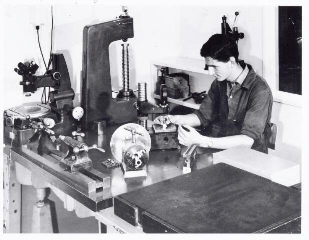 038582 - Volt. Noord. Opleidingen. Foto hing op tentoonstelling 25 jaar vakliedenopleiding Volt september 1964. Hier een vergelijkende meting m.b.v. eindmaten en een meetklok. Dit kon op 0,01 mm. nauwkeurig.