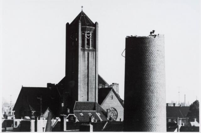 034128 - Het slopen van de schoorsteen van Volt Zuid in 1961. De sloop moest steen voor steen gebeuren omdat er geen plaats was om hem te doen omvallen. Het werk werd uitgevoerd door schoorsteen bouwbedrijf het Zuiden uit Tilburg. Op de achtergrond de kerk van Broekhoven I.