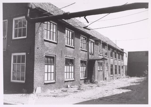 016883 - Gedeelte van het fabriekscomplex van looierij/wolwasserij Bernard Pessers. Ledermagazijn met afdeling expeditie. In het gebouw bevonden zich ook spreekkamers en was er een douche- en wasgelegenheid voor het personeel. Op de achtergrond een deel van de looierij.