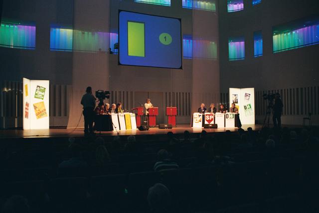 1237_002_221-1_003 - Politiek. Een vergadering voor de gemeenteraadsverkiezingen in de Tilburgse concertzaal in 1999. Een debat met R. van Gurp (GroenLinks), W. Luijendijk (PvdA), G. Schriek (A.B.T.), Els Aarts Engbers (CDA), B. Stok (VVD), Tiny Kox (SP), A. van Zijl (Algemeen Belang) en H. Dieteren (D66).