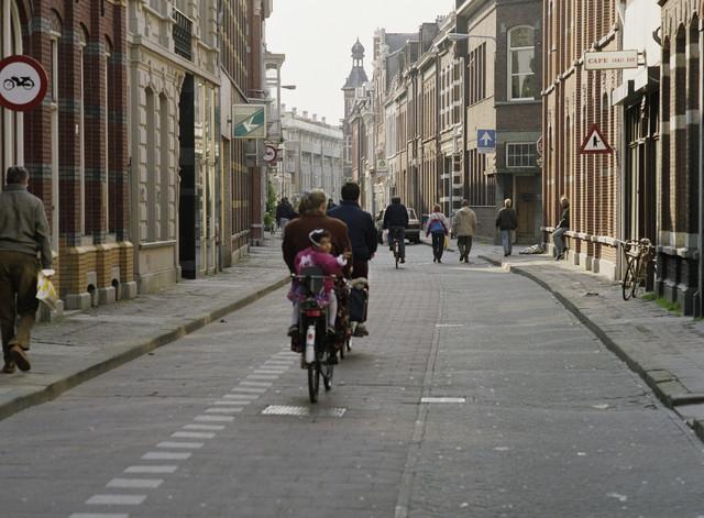 """TLB023000170_001 - Tuinstraat met fietsers en wandelaars. Op de hoek van de Langestraat (rechts op de foto) was t/m 1970 """"Drukkerij Roomsch Leven"""" gevestigd. Aan de rechterkant (nr. 59) was Café Zanzi Bar gevestigd.  Foto genomen in kader """"SPB / BouwRai"""" ter promotie van het """"Samenwerkingsverband Praktijkopleiding Bouw"""" en de tweejaarlijkse bouwmaterialenbeurs in de Amsterdamse RAI."""