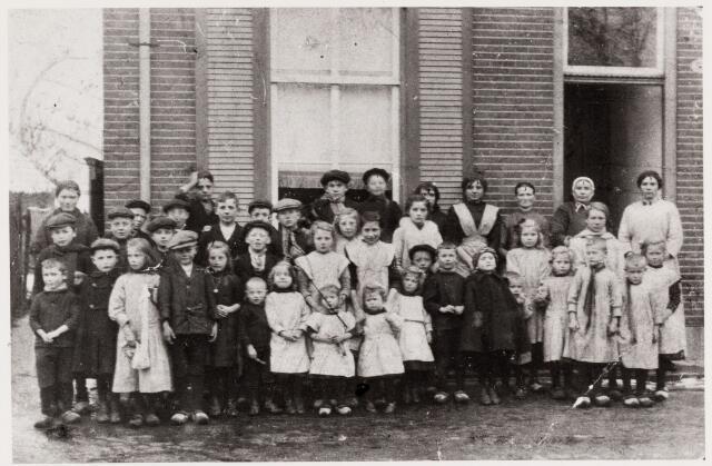 """049680 - Hasseltstraat nr. 23. Het huis waar deze kinderen (die net uit school kwamen) voorstaan, was verhuurd door dhr. Groenendaal aan Cornelis """"de zwarte"""" de Groot en Sieke de Groot -Janssen. Zij staat helemaal bovenaan derde van rechts. Hun kinderen staan tussen de andere kinderen in. Harrie de Groot (geb. 04-05-1907 en overl. 08-02-1978) staat onder, zevende van rechts."""
