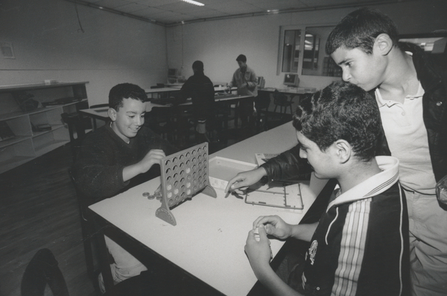 """651272 - Mooi zo, Goed zo. Jongens spelen spel """"vier op een rij"""" in het Marokkaans Jongeren Adviescentrum Het MJAC kreeg van verschillende Tilburgse organisaties o.a. computers, tweedehands meubilair en hobbymaterialen."""
