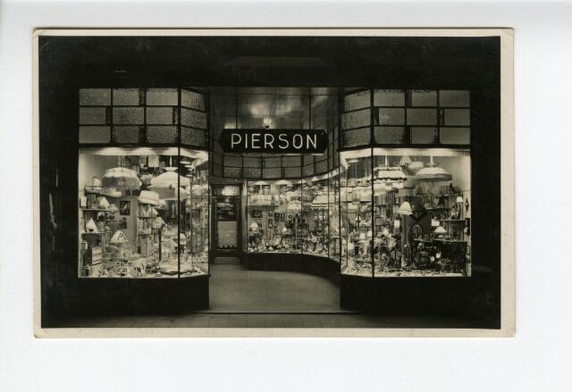 604210 - Etalage en portiek van de firma Pierson. Pierson was een winkel in galanteriën en luxe artikelen, gevestigd aan de Heuvelstraat 99 en opgericht door Everardus Petrus Pierson (1853-1900). De oprichter overleed in 1900, hierna werd de zaak voortgezet door zijn weduwe Anna Pierson-van Laarhoven. De weduwe werd geassisteerd en vervolgens opgevolgd door haar zoon Cornelis Petrus Johannes Pierson (1883-1948). De winkel aan de Heuvelstraat handelde in verlichtingen, huishoudelijke artikelen, luxe artikelen, glas, kristal en porselein.  De foto is zeer gedetailleerd en toont duidelijk de inhoud van de etalage, zoals lampen, serviesgoed, barometers, kammenbakjes en heiligenbeelden.