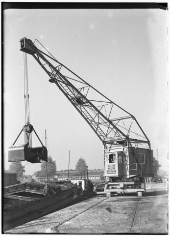 050957 - Het lossen van een schip in de Piushaven met een hijskraan van de firma G.B. Sanders uit Enschede.