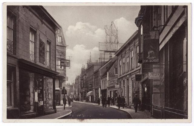 001139 - Heuvelstraat ter hoogte van de Willem II-straat richting Heuvel. Links kledingmagazijn 'de Duif' rechts ijzerwarenhandel W. v.d. Schoot.