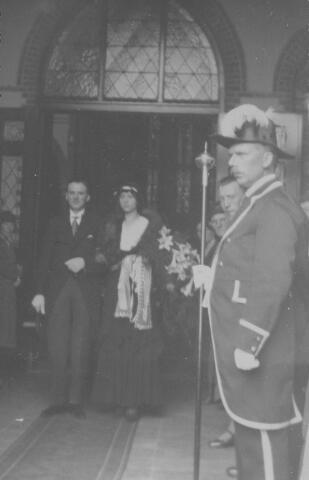 063869 - Het bruidspaar Cornelis Josephus Maria (Kees) van Belkom, geboren te Tilburg op 27 september 1905, en Berta Henrica Cornelia van Noort, geboren te Tilburg op 19 februari 1906, verlaat de Besterdse kerk na de huwelijkssluiting. Rechts op de voorgrond suisse Jan van Gils. Hij was de opvolger van Harrie van Belkom, de vader van bruidegom Kees van Belkom.