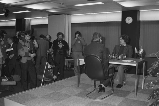 TLB023002429_002 - Deze heren spelen een schaakpartij, waarbij er ook media aandacht is en er wordt door de NOS gefilmd